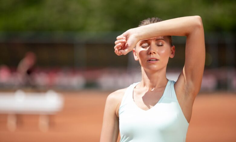 Exhausted woman is wiping sweat after workout outdoor